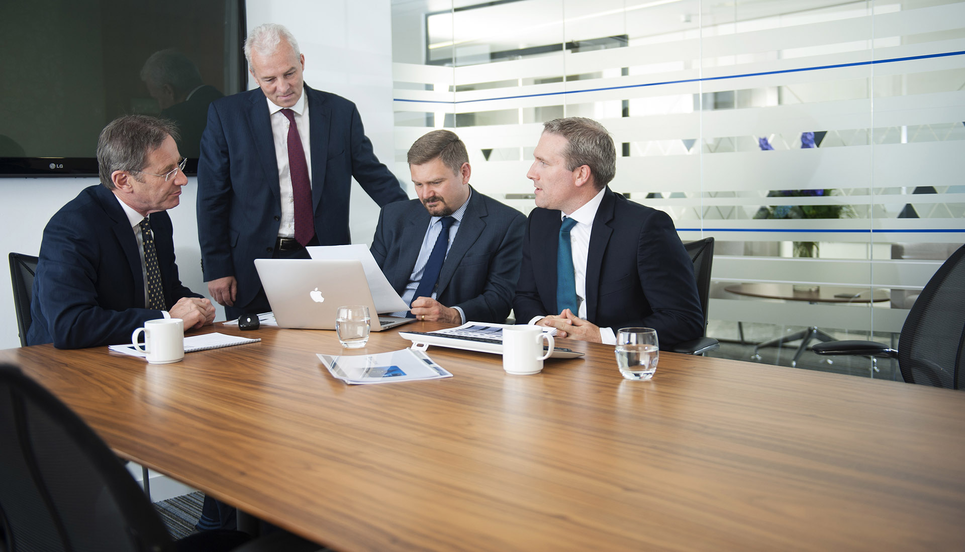 A group of businessmen conduct a meeting in a boardroom in Manchester.