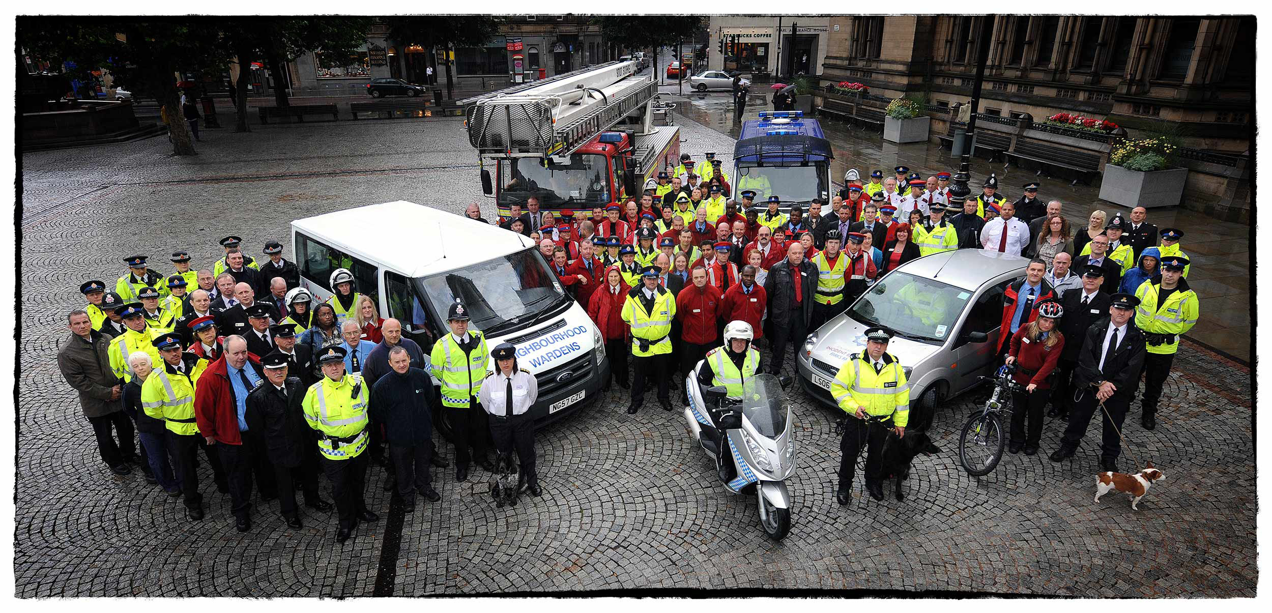 Members of the police, fire, ambulance and rescue services pose for a photograph at Manchester Town Hall.
