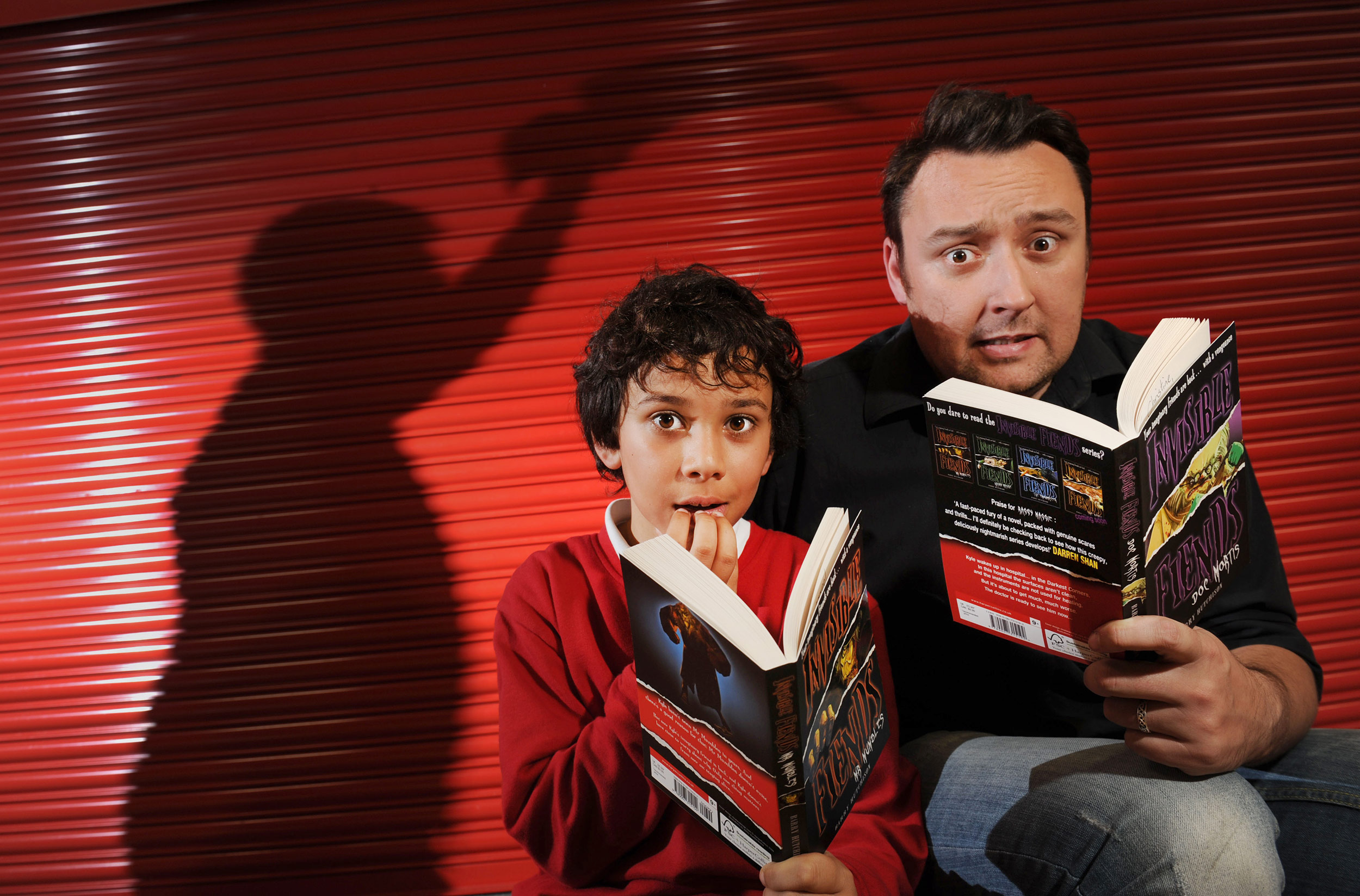 A writer visits a school in Manchester and poses for photographs with the children and his new book.