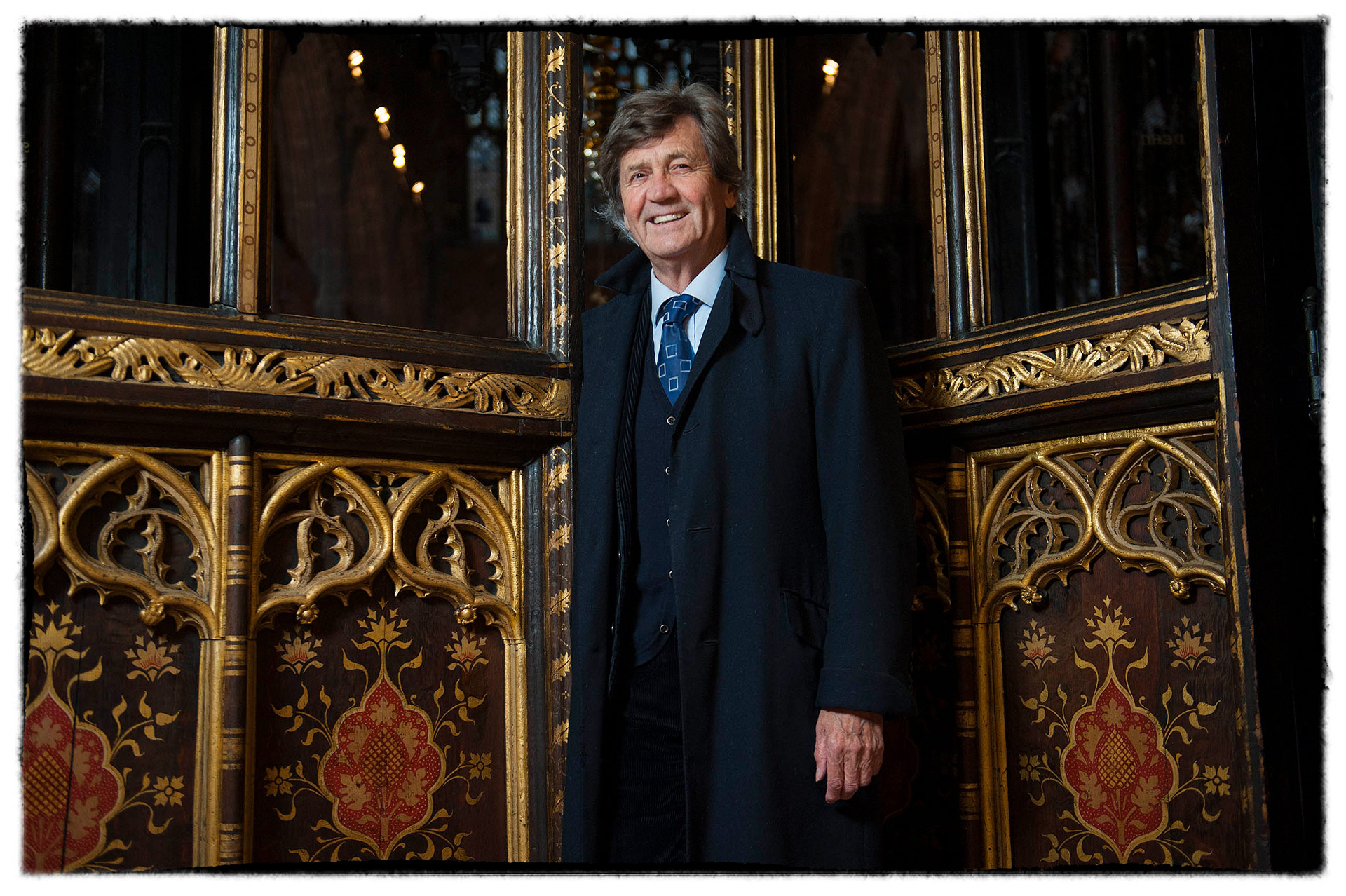TV personality Melvyn Bragg stands between the choir stall doors at Manchester Cathedral.