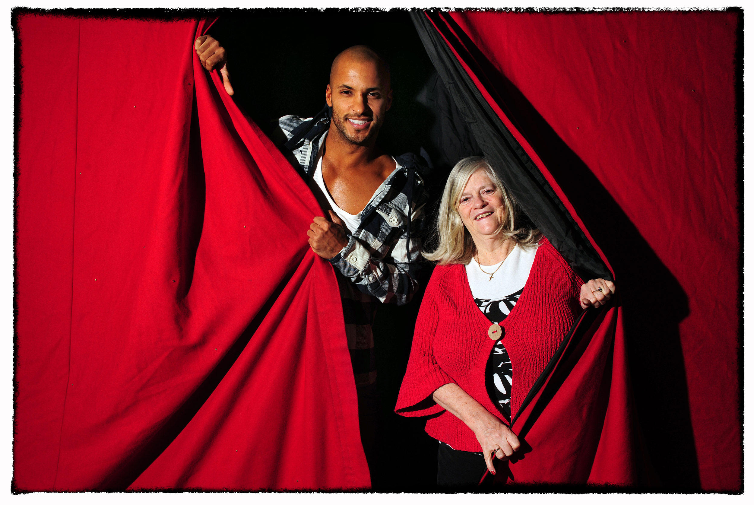 Two BBC TV stars poses for publicity photographs and peer through a curtain at Manchester's Arena.