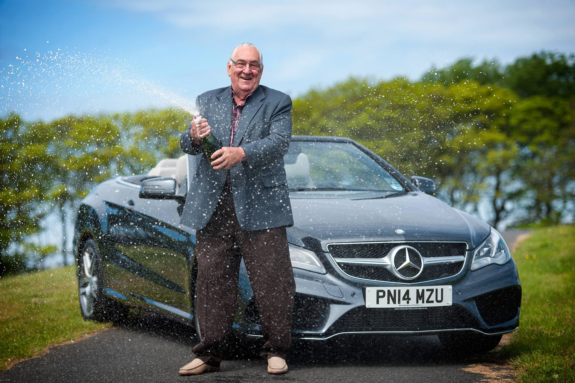 A man wins the Lotto and poses with his new car whilst celebrating with champagne.