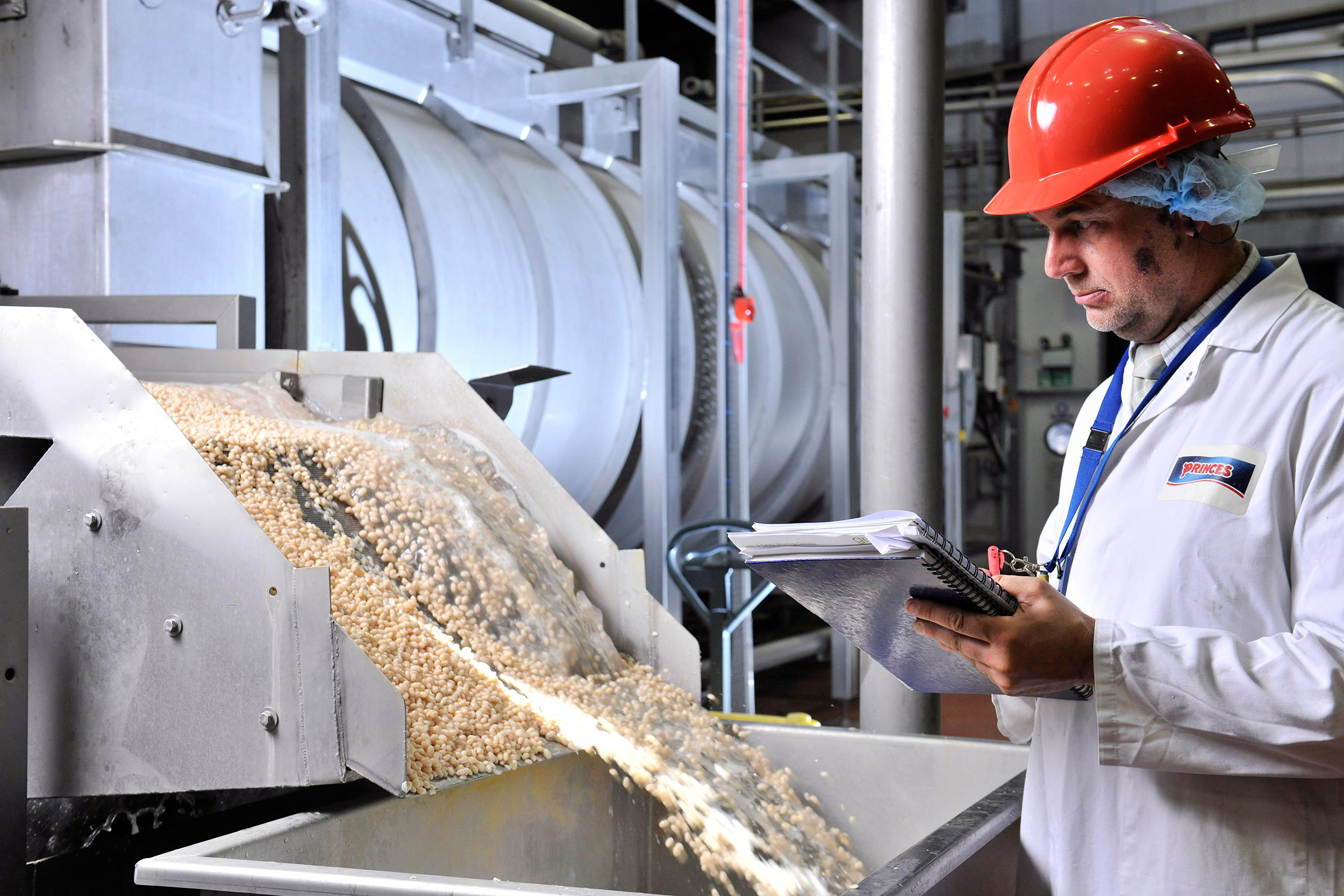 A man monitors a food production line at a Princes UK factory. Food manufacturing photographer Manchester photographer