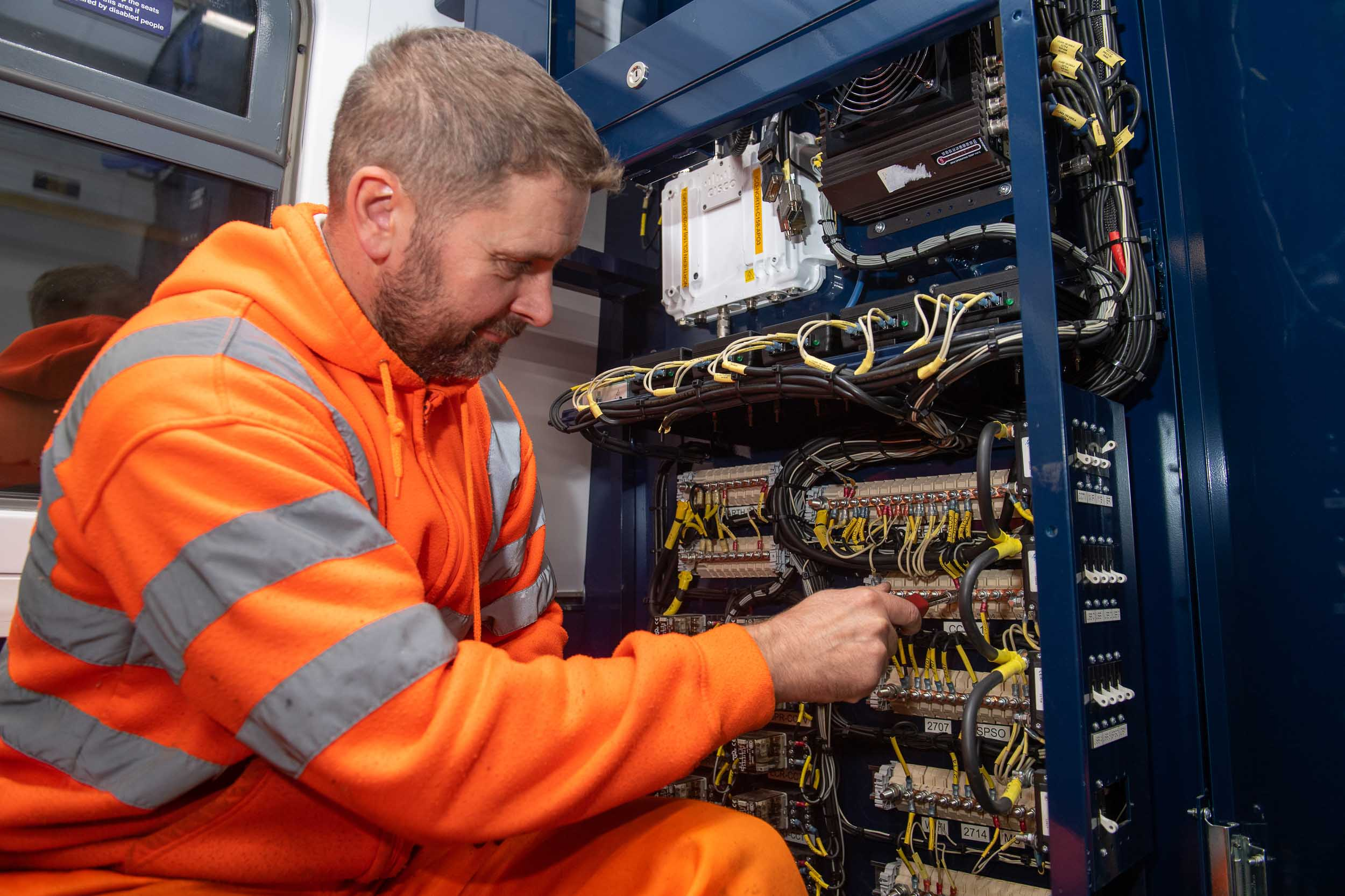 An engineer is photographed as he installs hardware to a new digital train.
