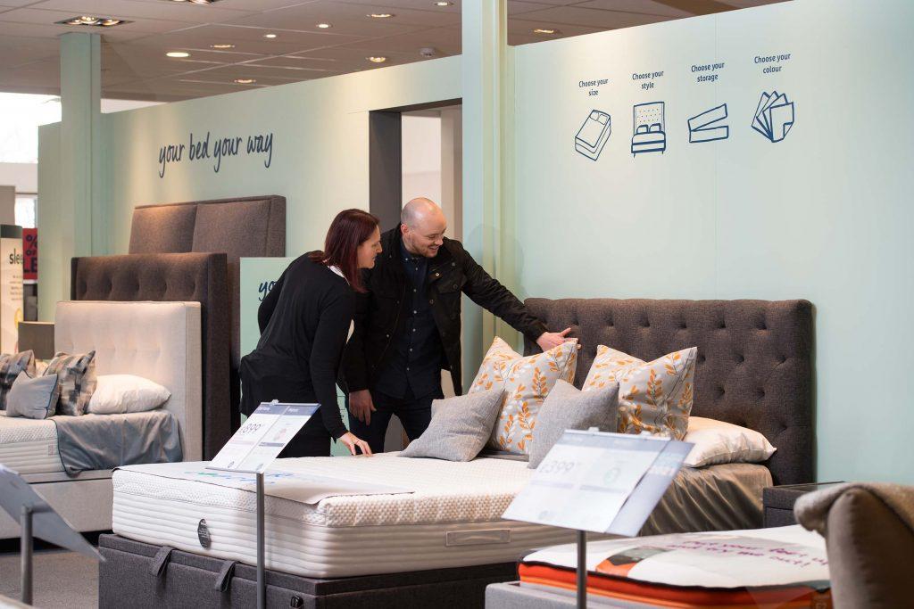 Customers looking at bespoke beds in Harveys Furniture